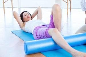 Trainer working with woman on exercise mat photo