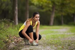 atleta atando los cordones de sus zapatos