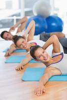 Smiling people doing pilate exercises in fitness studio