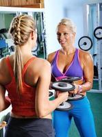 duas belas mulheres exercitando na academia com pesos