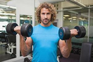 Handsome young man exercising with dumbbells in gym photo