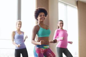 group of smiling people dancing in gym or studio photo