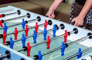 caucasian male playing table soccer football game photo