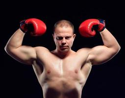 Muscular young caucasian boxer wearing boxing gloves