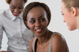 mujer caucásica y dos mujeres negras sonriendo