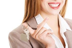 joven mujer caucásica de negocios tiene llaves de casa. foto