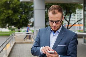 Caucasian businessman outside office using mobile phone.