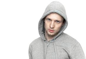 Young Caucasian man in gray jacket with hood. Portrait isolated photo