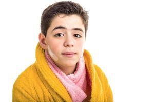 chico caucásico de piel suave en bata de baño amarilla y toalla rosa foto