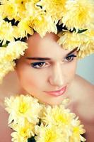 mujer caucásica con corona de flores amarillas alrededor de su cabeza