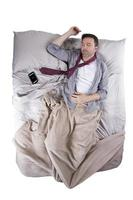 Caucasian Man Sleeping with Cell Phone Alarm in Bed