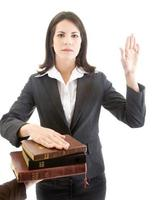 Caucasian Woman Swearing on Stack of Bibles Isolated White Background photo