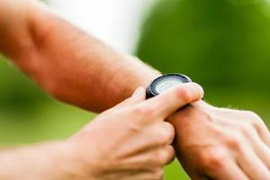 Trail runner looking at sport watch photo