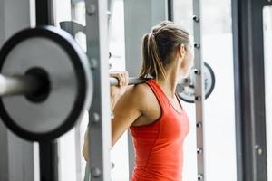 Young beautiful woman lifting weights in a gym photo