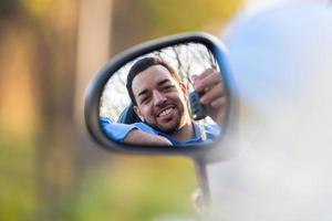 Young latin american driver holding car keys driving his n photo