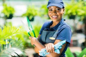 jardineiro americano africano, segurando a ferramenta de jardim