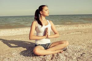 mujer joven practicando yoga o fitness en la orilla del mar foto