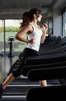 Woman running on treadmill in an empty gym