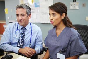 médico con enfermera trabajando en la estación de enfermeras