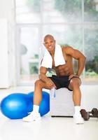 hombre musculoso afroamericano relajante en el gimnasio foto