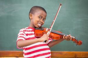 alumno feliz tocando el violín en el aula foto