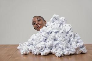 Mujer de negocios africanos con arrugado montón de papeles en el lugar de trabajo