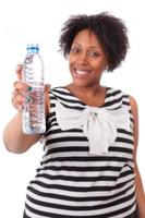 Overweight young black woman holding an water bottle