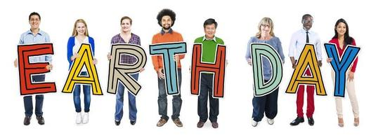 Cheerful and Diverse People Holding Text Earth Day photo