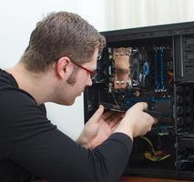 Técnico masculino reparar computadora en la tienda foto