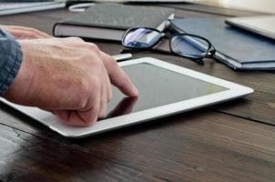 Man clicks on screen tablet computer closeup photo