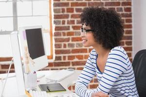 sonriente editor de fotos usando la computadora en la oficina