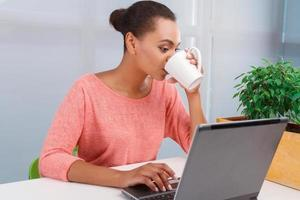 Pretty mulatto girl working on computer photo