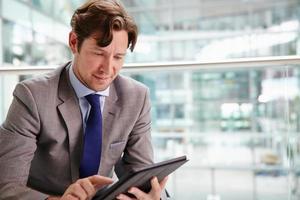 Corporate businessman using tablet computer, waist up