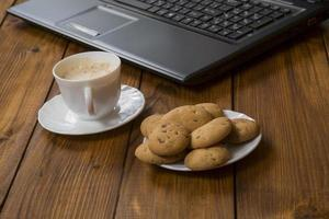computer a cup of coffee and cookies