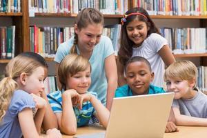 élèves mignons à l'aide de la tablette tactile dans la bibliothèque