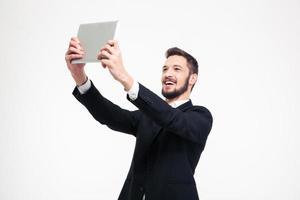 Businessman making selfie photo on tablet computer