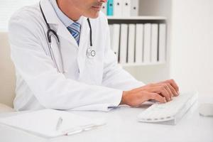 Doctor typing on keyboard and photo