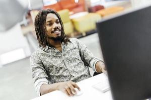 Black handsome designer workin on a computer