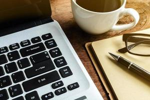 Ordenador portátil y una taza de café en la mesa de madera vieja