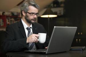 hombre de negocios en casa usando una computadora portátil foto