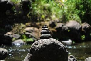 rocas apiladas a través del río en hawaii foto