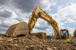 excavadora delante de un cielo nublado foto