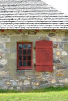 red trimmed window and shutter against stone photo