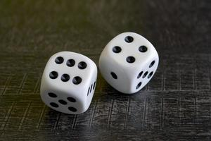 Two white dice gamble on a background photo