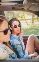 Dos mujeres jóvenes descansando sentados dentro del coche