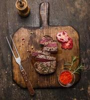 roasted  ribeye steak sliced on a cutting board