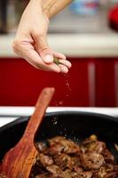 Chef's hand sprinkling spice mix