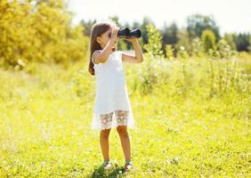 Little girl looks in binoculars sunny summer