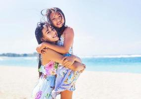 two asian sisters on a beach photo