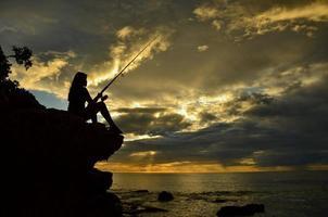 Silueta chica pescando en un acantilado en Hawaii